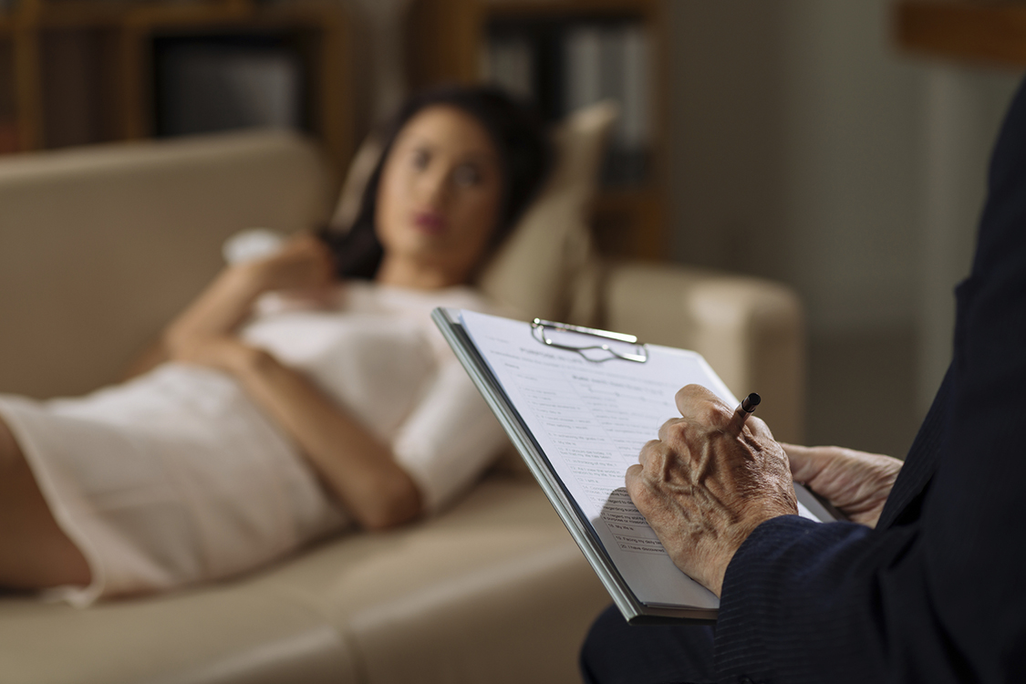 Mature psychiatrist making notes during the session with female client